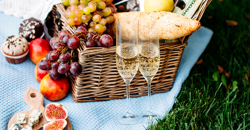 Wicker picnic basket overflowing with fresh fruit and two glasses of champagne