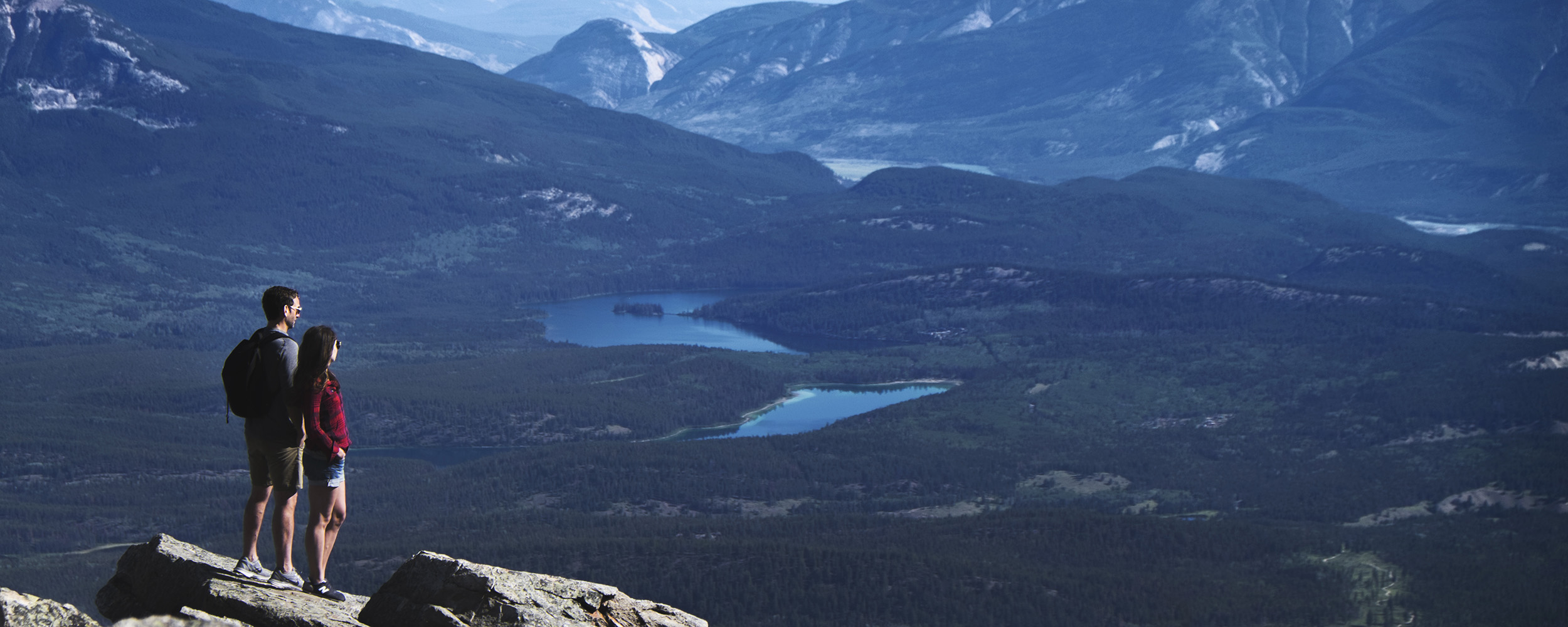 A couple looks out over the Jasper valley from an alpine view point