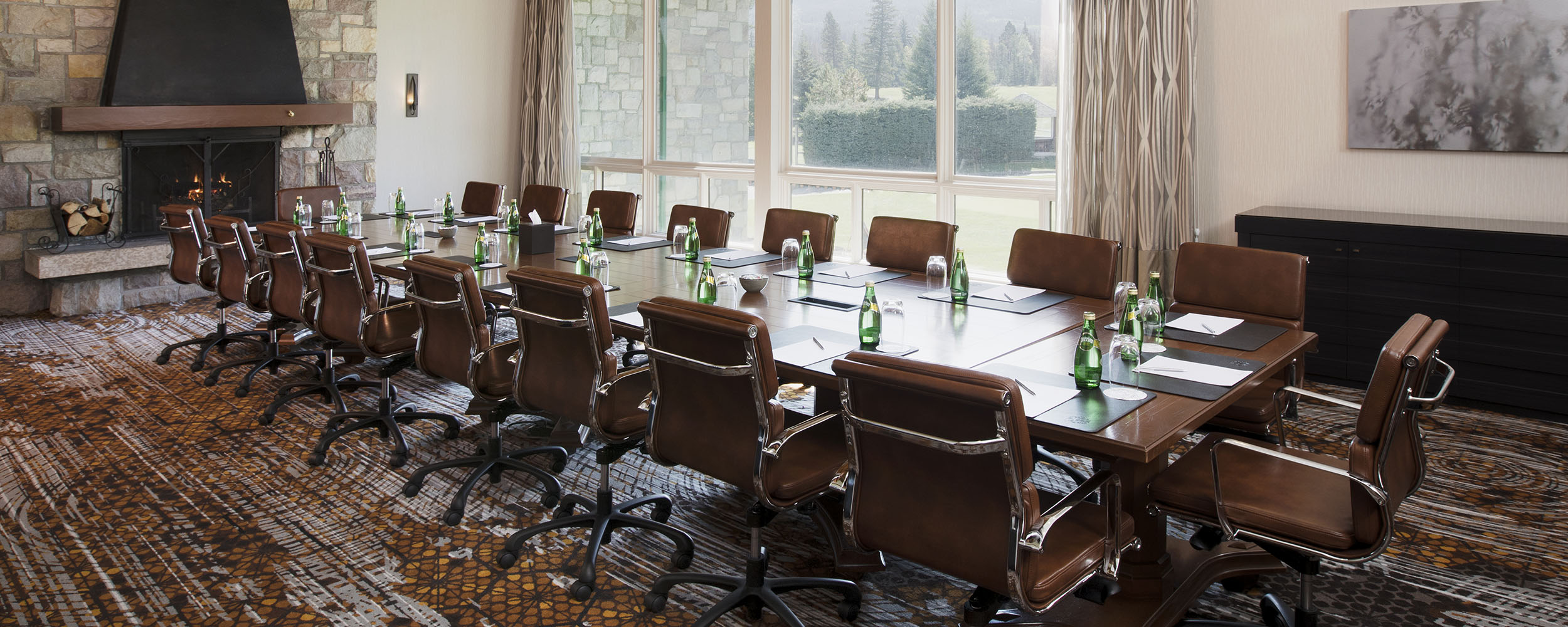 Thompson Boardroom with Fireplace and Large Windows Set for a Meeting