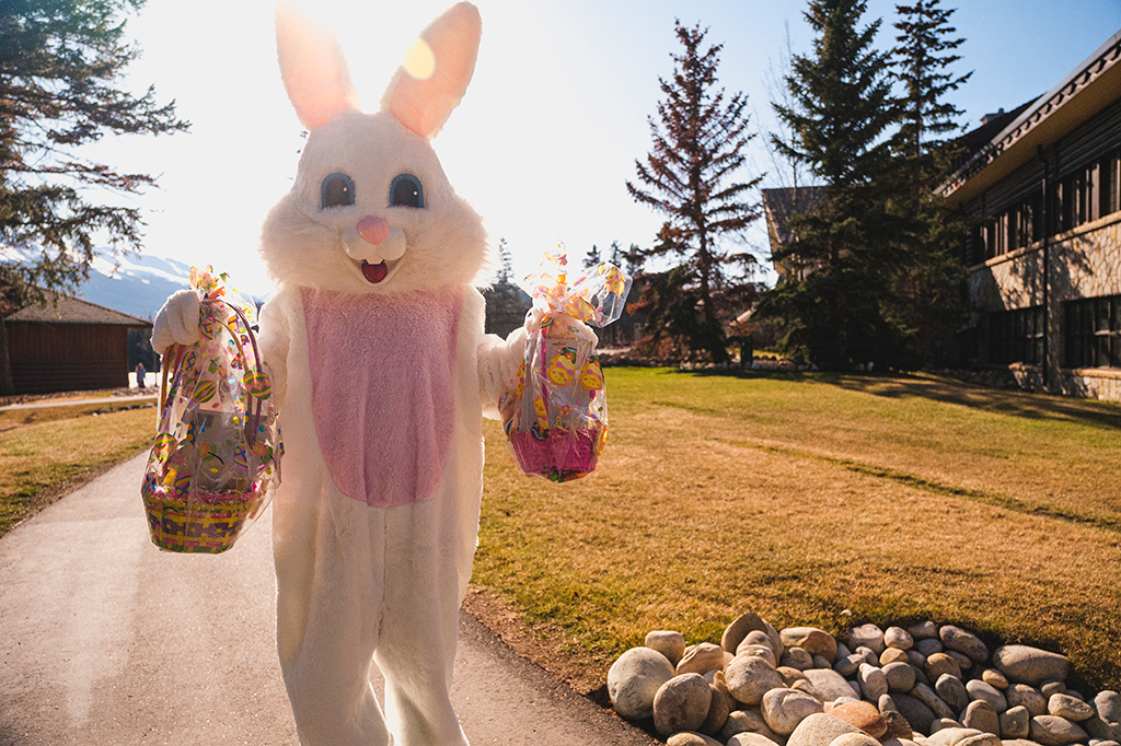 The Easter Bunny stands outside the lodge in the sunshine holding baskets of treats.