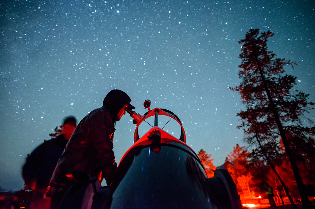 A man prepares to look through a large telescope at the stars.