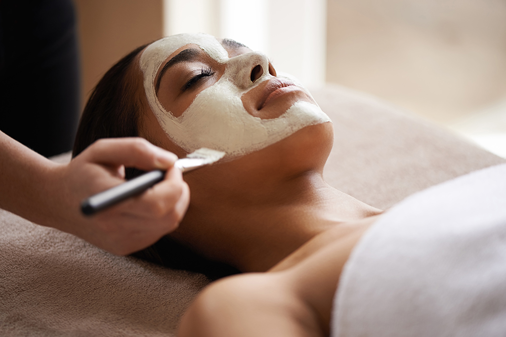 A woman enjoys a spa treatment as a clay is carefully applied to her face.