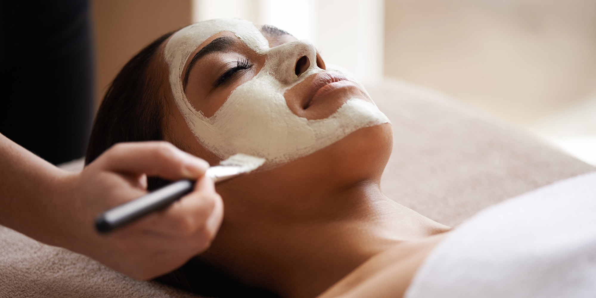A woman has a clay mask applied using a brush