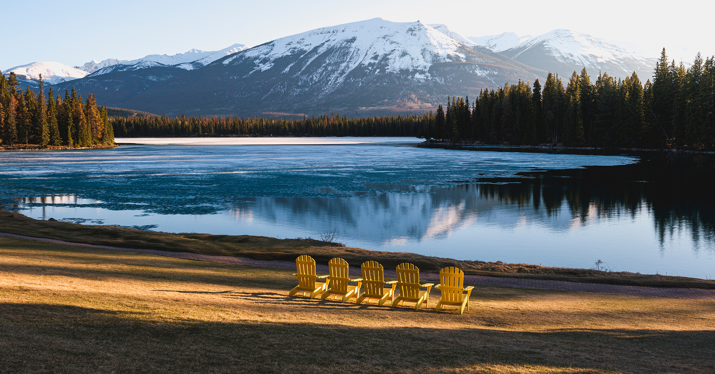 Yellow Adirondack charis sit on the sunny shores of Lac Beauvert as the winter ice melts.