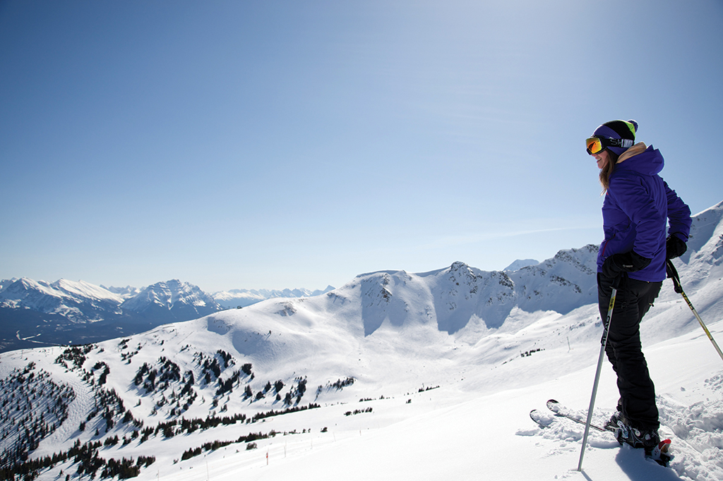 A woman stand at the top of a ski hill in the sun.