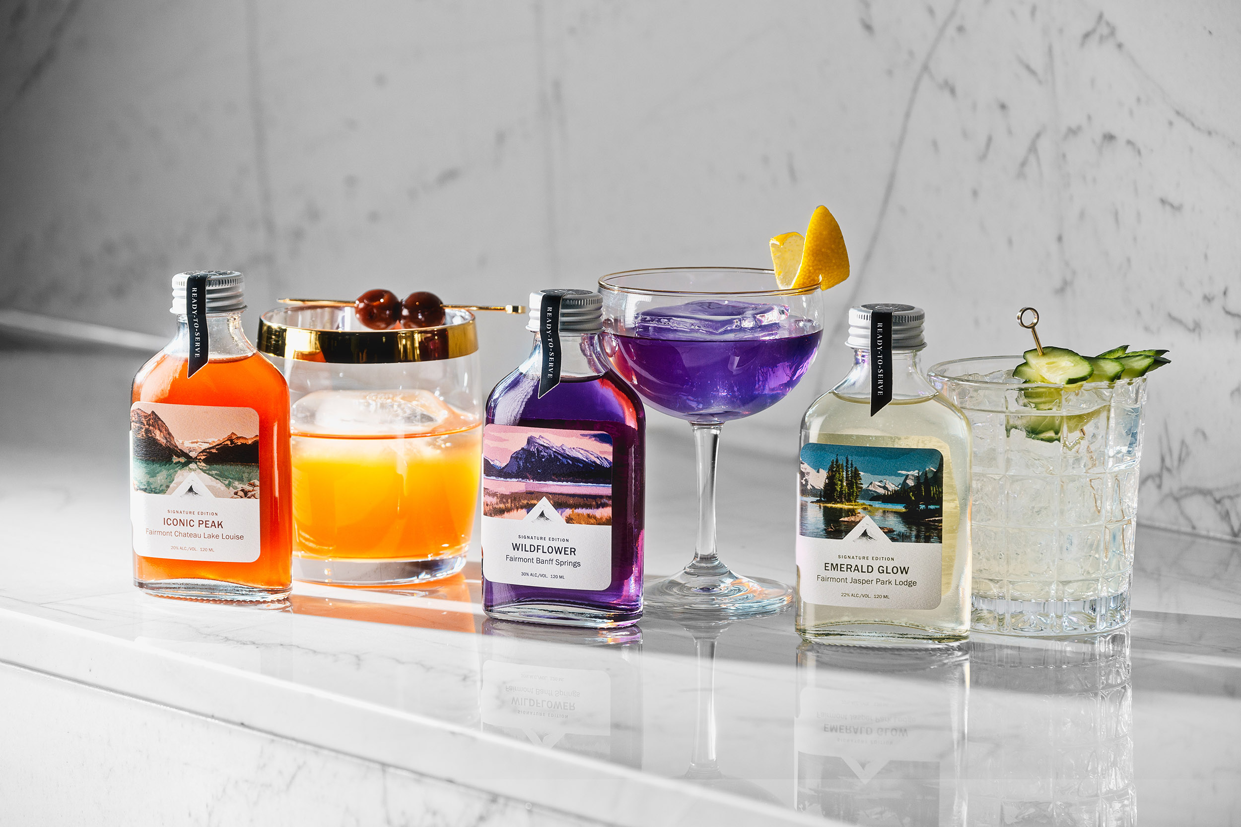 A collection of three bottled cocktails from Fairmont Hotels in Canada's Western Mountain Region are displayed in bright light with colours of orange, purple and pale green.