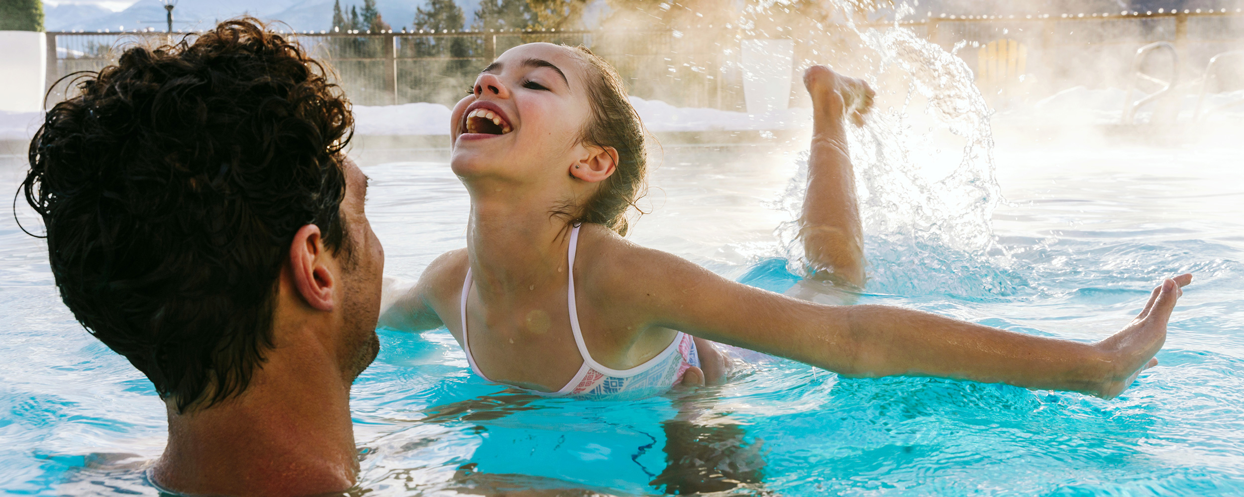 A father splashes with his daughter in Fairmont Jasper Park Lodge's heated outdoor pool with mountains blurred in the background.